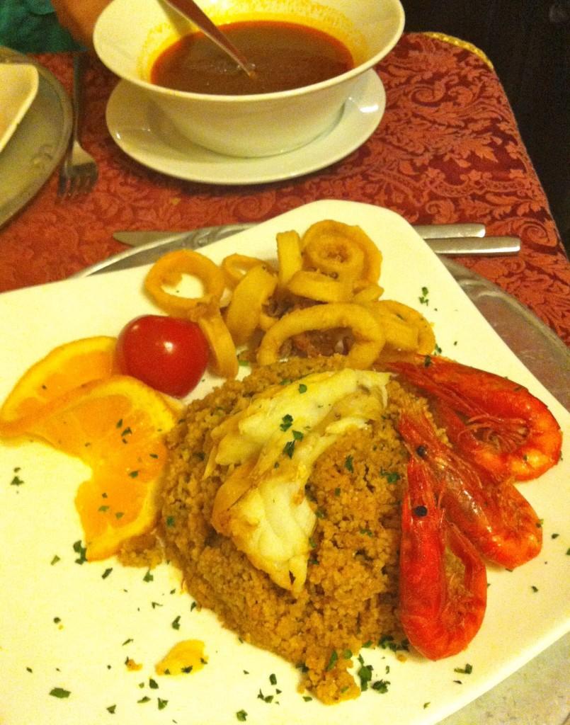 Cous Cous a base di pesce e tranci di dentice, con gamberi e calamari fritti, brodo di pesce.